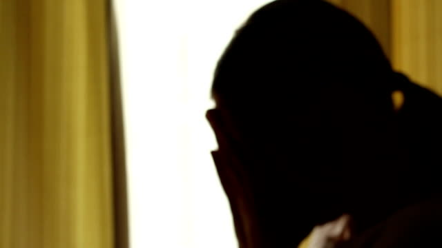 Silhouette of a girl at the window, defocused video