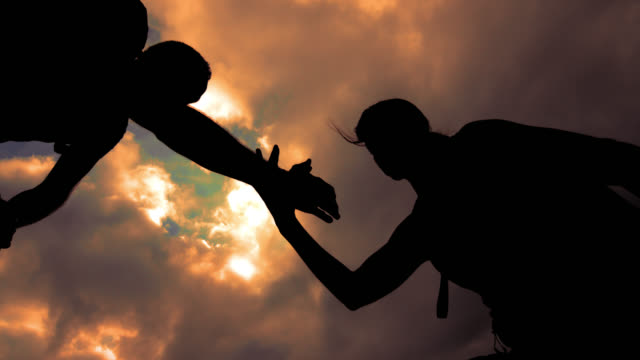 SLO MO silhouette of a helping hand to the woman mountaineer video