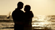 Silhouette of a loving couple, hugging at sunset near the sea. Sailboat floats in the distance video