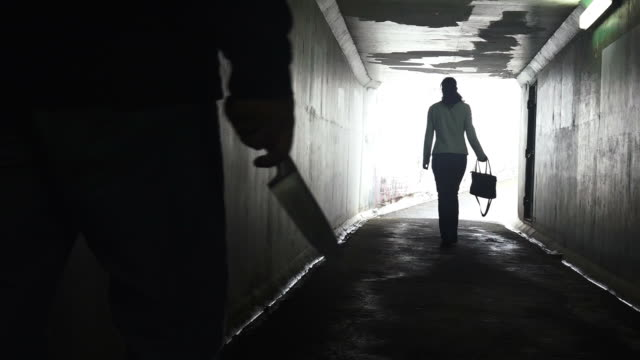 Silhouette of a man carry a knife follows a young woman in a dark tunnel video