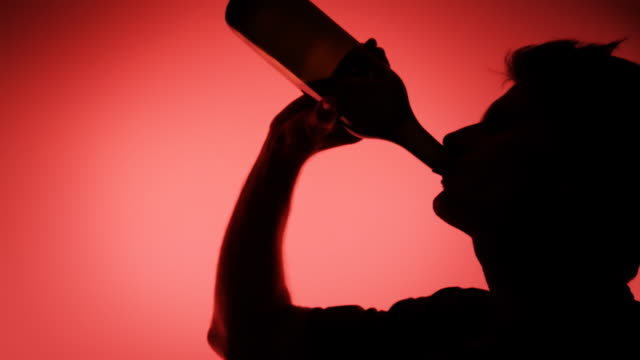 HD: Silhouette of A Man Drinking From Bottle video