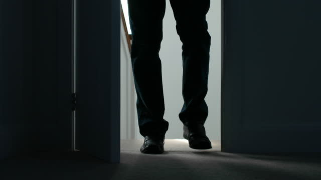 Silhouette of a man opening a door and entering a dark room. video