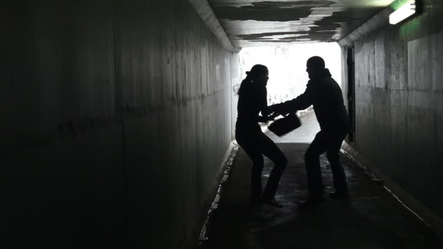 Silhouette of a man thief steals a bag from a woman in a dark tunnel video