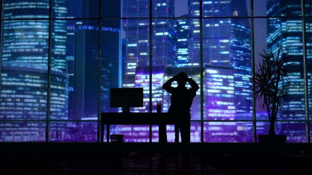Silhouette of a man working late in the office at the computer video