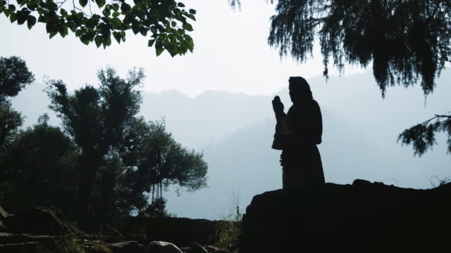 Silhouette of a praying man in a hoodie on nature background video