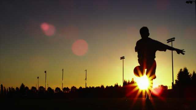 Silhouette of a soccer player juggling a ball video
