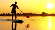 SLO MO Silhouette of a stand-up paddleboarder video