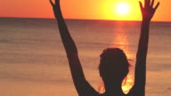 Silhouette of a woman at sunset with ocean. video