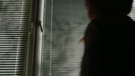 Silhouette of a woman coming to the window and opening the blinds video