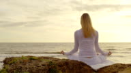 Silhouette of a woman meditating at the beach at sunrise video