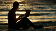 Silhouette of a young man sitting on the beach at sunset. It uses laptop video