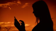 Silhouette of an adult girl against the sky, woman with long hair prints a message on a mobile phone. It uses a gadget to communicate with friends video