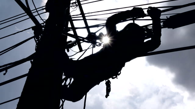 Silhouette of an electrician climbing a newly installed utility pole video