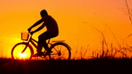 Silhouette of boy and bike video