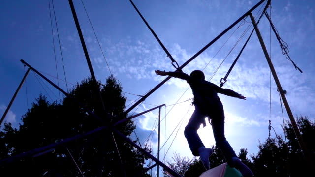 Silhouette of boy jumping on bungee trampoline video