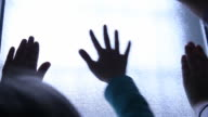 Silhouette of children hands on the light window. video