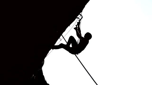 Silhouette of climber on a rock with complex route video
