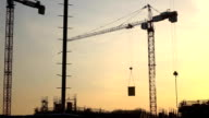 Silhouette of crane transferring concrete plate over construction site. FullHD shot video