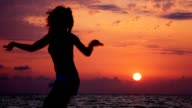 Silhouette of dancing woman on beach video