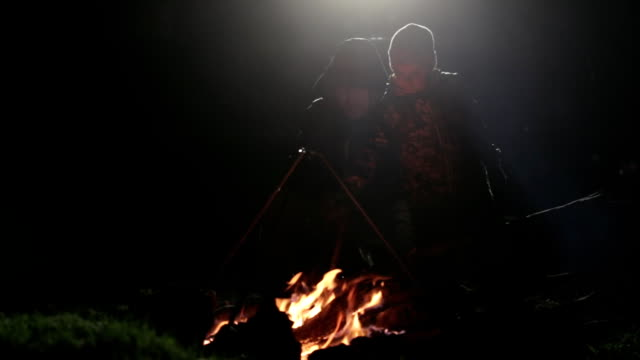 Silhouette of father and son next to bonfire in the night. video