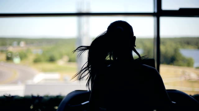 Silhouette of girl running on the treadmill video