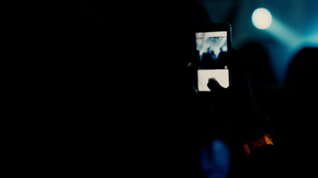 Silhouette of girl shoots video on a smartphone at the party video