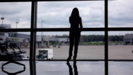 Silhouette of girl talk on phone, stand against full height window at airport video