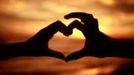 Silhouette of hands on beach at sunset making heart shape video