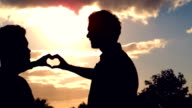 Silhouette of homosexual couple doing heart with hands together video