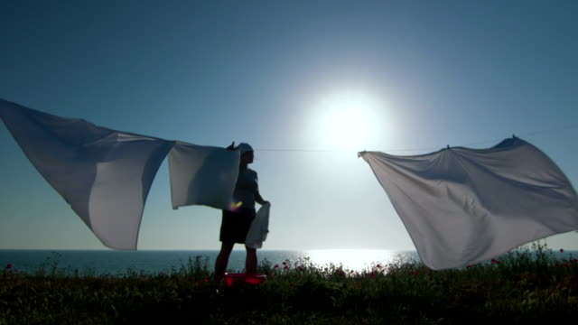 Silhouette of housewife and white laundry on a clothesline video
