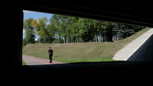 Silhouette of jumping athlete from the shadow of bridge to the open space with bright sun light. video