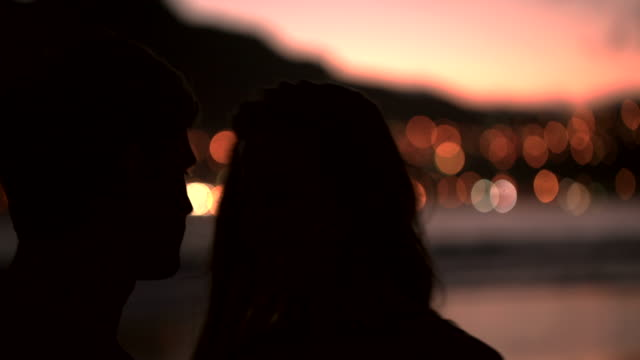 Silhouette of loving couple kissing on the beach video