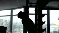 silhouette of male bodybuilder pulling up in a gym video