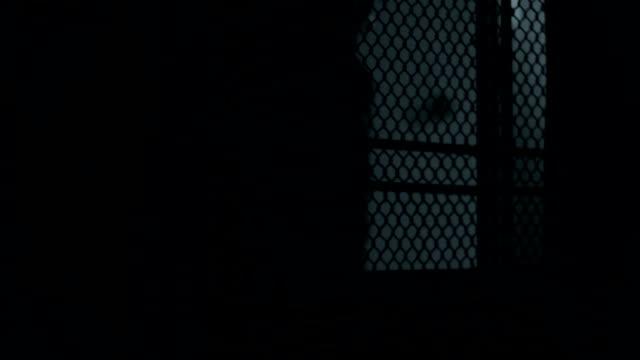 Silhouette of man figure opening door, dark scary thriller video