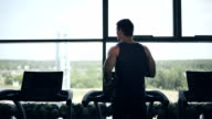 Silhouette of man running on the treadmill video