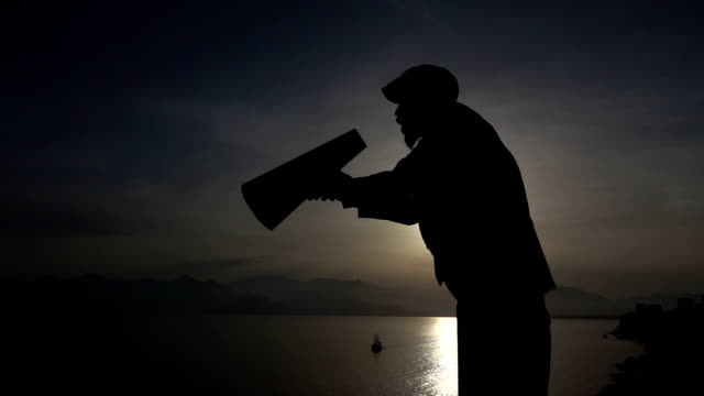 Silhouette Of Man Yelling Trough A Megaphone In Sunset video