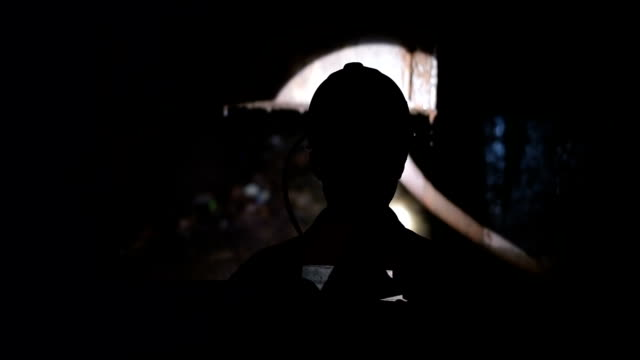 Silhouette of Miner go down into a mine shaft video