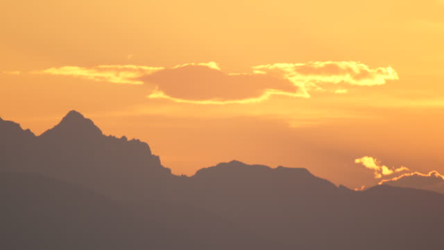 AERIAL: Silhouette of mountaintops in majestic European Alps over sky at sunset video