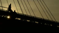 Silhouette of people crossing pedestrian bridge video