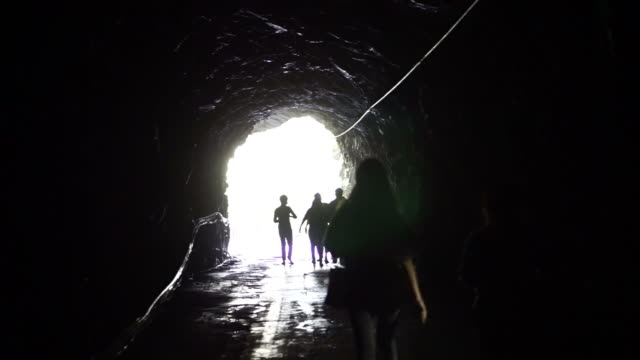 Silhouette of people go through the dark tunnel into the glowing end. Freedom and solution concept video