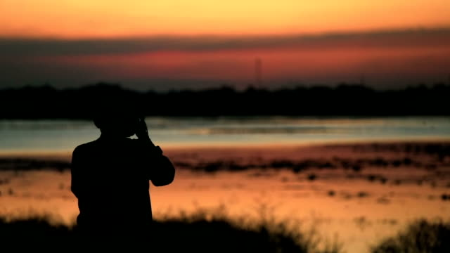 Silhouette of photographer against sunset, slow motion video