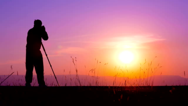 Silhouette of photographer against sunset video