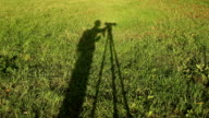 Silhouette of photographer with camera on tripod video