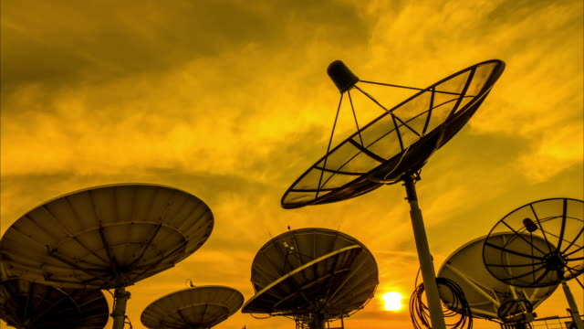 Silhouette of satellite dish and clouds in time-lapse video