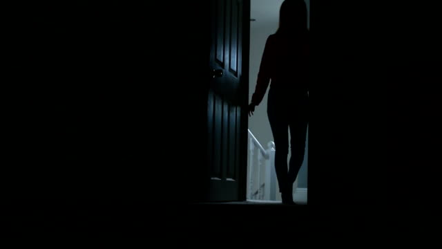 Silhouette of slim young female entering a dark room. video