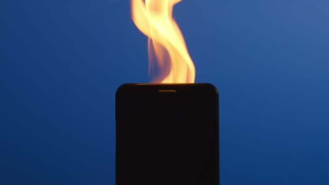 SLOW MOTION: Silhouette of smartphone burning video