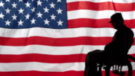 Silhouette of soldier in wheelchair front US flag video