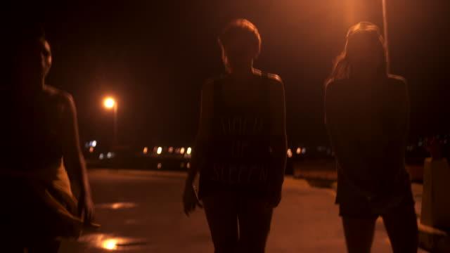 Silhouette of teen grunge girls walking under a street light video