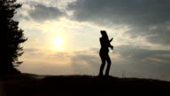 Silhouette of the girl dances against the sky and sun video
