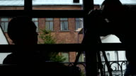 Silhouette of the photographer and the model in the light of the window. video